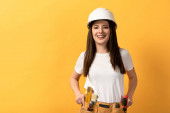 smiling handywoman in helmet looking at camera on yellow background