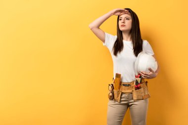 Serious handywoman holding helmet and looking away on yellow background stock vector