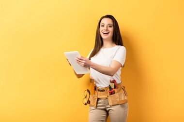 smiling handywoman holding digital tablet on yellow background with copy space