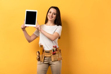 smiling handywoman holding digital tablet with copy space on yellow background