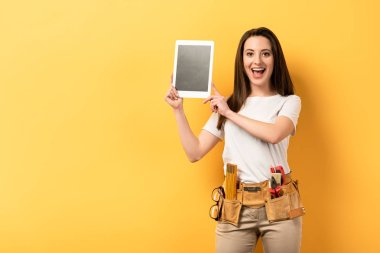 shocked handywoman holding digital tablet with copy space on yellow background