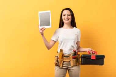 smiling handywoman holding digital tablet and toolbox on yellow background