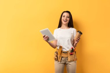 smiling handywoman holding paper cup and digital tablet on yellow background