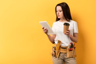 handywoman using digital tablet and holding paper cup on yellow background