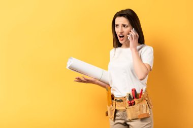 shocked handywoman talking on smartphone and holding project on yellow background