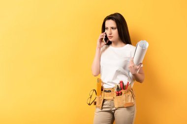 serious handywoman talking on smartphone and holding project on yellow background