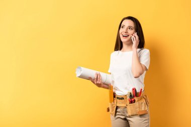 smiling handywoman holding smartphone and blueprint on yellow background