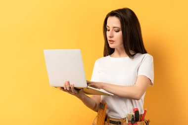 attractive handywoman using and holding laptop on yellow background