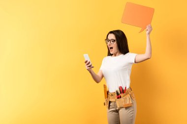 shocked repairwoman holding speech bubble and using smartphone on yellow background