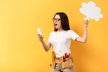 shocked repairwoman holding thought bubble and using smartphone on yellow background