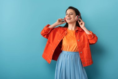 smiling woman with headphones listening to music on blue background