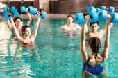 Selektivní zaměření trenéra držícího činky při cvičení vodní aerobik s lidmi v bazénu