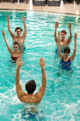 Pohled shora na trenéra, jak cvičí se skupinou mladých lidí během vodní aerobiku v bazénu