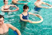Fotografie Vysoký úhel pohledu na mladé lidi trénink s bazénovými nudlemi v bazénu