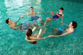 Vysoký úhel pohledu na usmívající se mladé lidi držící se za ruce při cvičení s bazénovými nudlemi v bazénu