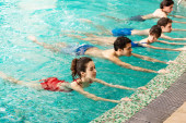 Photo Group of young people training together in swimming pool