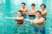 Photo Young people smiling at camera while training in swimming pool