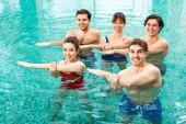Fotografie Mladí lidé se usmívají na kameru při tréninku v bazénu