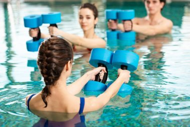 Selective focus of trainer holding barbells while exercising water aerobics with man and woman in swimming pool stock vector