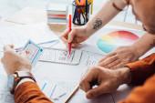 Selektivní zaměření návrhářů uxu pracujících s rozložením aplikací a barevným kruhem u stolu v kanceláři