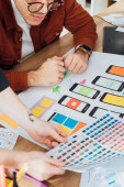 Cropped view of designers with color palette planning user experience design at table