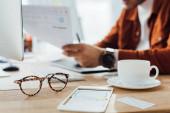 A szemüveg szelektív fókusza és a ux design elrendezése asztalnál dolgozó tervező közelében