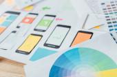 Selektiver Fokus auf Farbkreis und Vorlagen mit Gestaltung der mobilen Website auf Holztisch