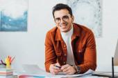 Tvůrčí designér se usmívá do kamery při práci na projektu uživatelského designu u stolu v kanceláři