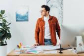 Dizájner néz el közelében szerkentyűk, színes körök és elrendezése felhasználói élmény design az asztalon