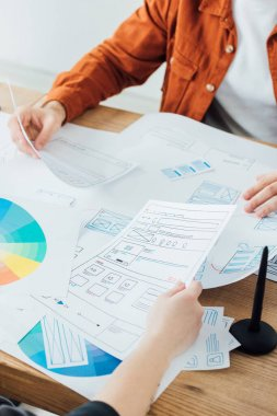 Cropped view of developers planning ux project near color circles on table stock vector
