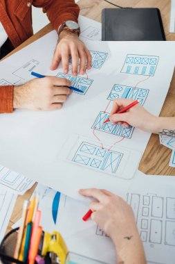 Cropped view of ux designers working with layouts and sketches on table stock vector