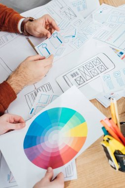 Cropped view of designers working with templates of ux design and color circle on table stock vector