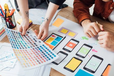 Cropped view of designers planning user experience design with color palette and website sketches on table stock vector
