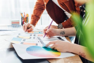 Selective focus of developers using website sketches and color circle while planning ux project stock vector