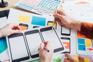 Cropped view of creative designers using mobile frameworks for user experience design of website on table stock vector
