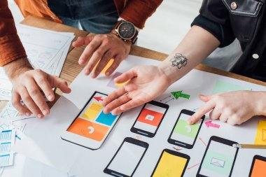 Cropped view of ux designers working with sketches and mobile wireframe layouts at table stock vector