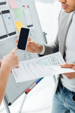 Cropped view of designer pointing on smartphone near colleague with templates of ux design near whiteboard in office stock vector