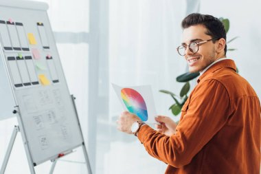 Selective focus of smiling ux designer holding color circle near layouts of mobile website design on whiteboard in office