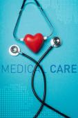 Draufsicht auf dekoratives rotes Herz mit schwarzem Stethoskop auf blauem Hintergrund, Darstellung der medizinischen Versorgung