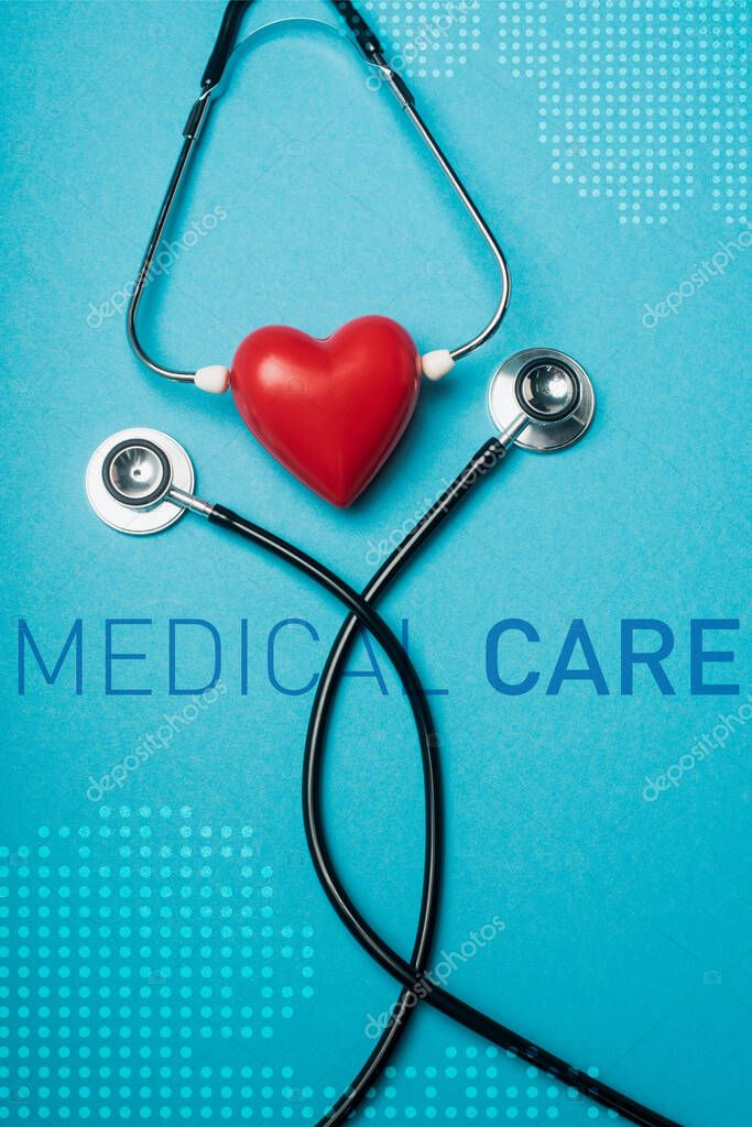 Top view of decorative red heart with black stethoscope on blue background, medical care illustration stock vector