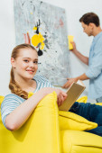 Photo Selective focus of girl with book smiling at camera near boyfriend cleaning painting in living room
