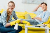 Selektivní zaměření ženy s úsměvem pryč při čištění konferenčního stolku s čisticím prostředkem a hadrem v blízkosti přítele s notebookem na gauči