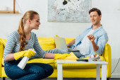 Side view of man with laptop pointing with finger on coffee table near smiling girl with detergent and rag in living room
