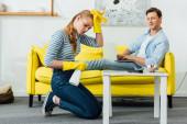 Boční pohled usměvavý muž s notebookem při pohledu na unavenou přítelkyni s čisticí prostředky v obývacím pokoji