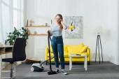 Atraktivní usmívající se žena ve sluchátkách čistící koberec s vysavačem doma