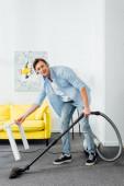 Usmívající se muž ve sluchátkách při pohledu na kameru při čištění koberce s vysavačem v obývacím pokoji