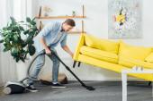Boční pohled na člověka zvedání pohovka při čištění koberce s vysavačem v obývacím pokoji