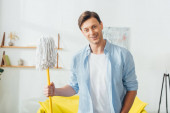 Handsome man smiling at camera and holding mop in living room