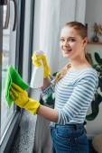 Seitenansicht einer lächelnden Frau, die beim Fensterputzen zu Hause in die Kamera schaut