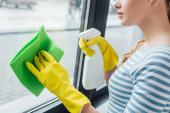 Oříznutý pohled na ženu pomocí hadru a čisticího prostředku při čištění okna doma